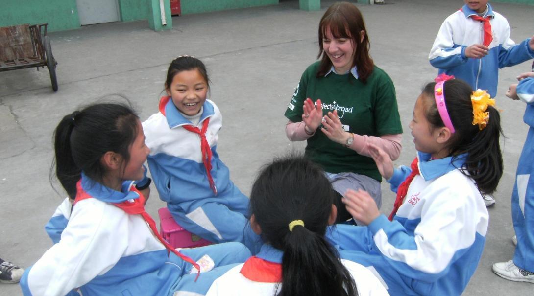A volunteers doing teenage community work in China, plays a game with children on the playground.